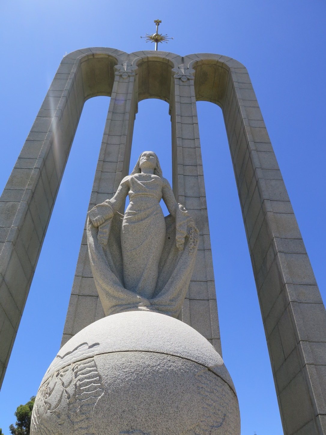 Franschhoek The Huguenot Monument near the Huguenot Museum, Huguenot woman standing on globe with three arches and blue sky