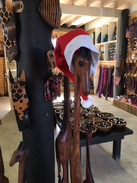 wooden giraffe statue with red and white father christmas santa hat