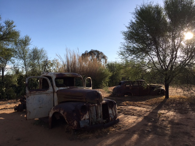 Rusting vehicles in Namibian desert town.