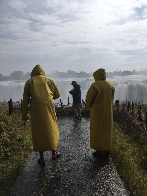 At the edge of Victoria Falls, three men, two of them wearing long yellow raincoats.