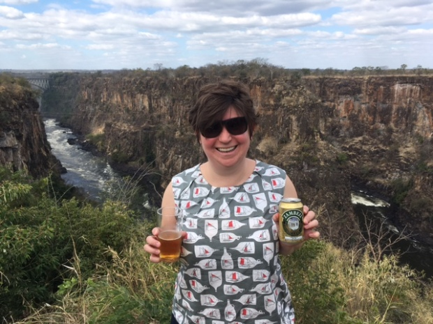 Woman drinking a Zambezi Beer by the Zambezi overlooking the Batoko gorge. River in Zimbabwe with Zambia in the background