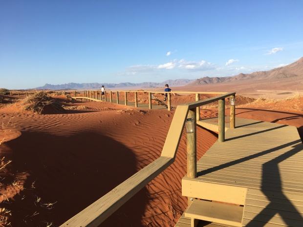 Two children on boardwalk through Nambian desert on family road trip.