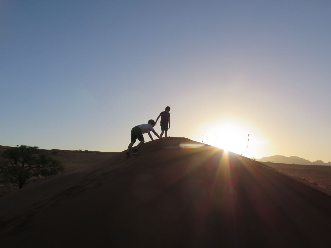 Kids climbing sand dune at sunset, Namibia.