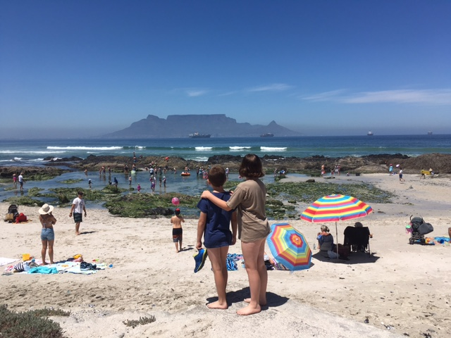 People on beach looking at Table mountain from Bloubergstrand