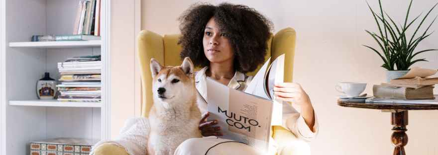 woman in armchair with dog reading magazine